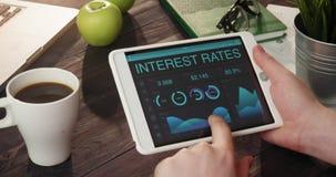 Comprobación de datos de los tipos de interés usando la tableta metrajes