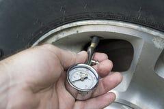 Comprobación de la presión de aire en vehículos Fotos de archivo libres de regalías