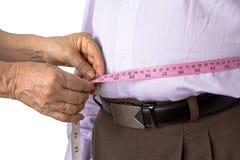 Comprobación de las grasas de cuerpo con la cinta métrica Fotografía de archivo libre de regalías