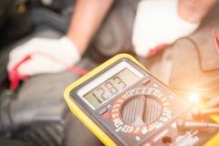 Comprobación de voltaje de la batería de coche Imagen de archivo