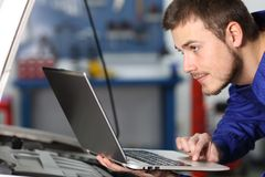 Comprobación del mecánico de coche electrónica con un ordenador portátil Foto de archivo