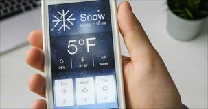 Comprobación del wather usando el smartphone app Nevado y frío metrajes
