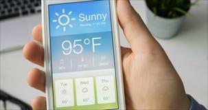 Comprobación del wather usando el smartphone app Tiempo caliente y soleado almacen de video