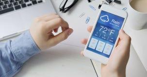 Comprobación del wather usando el smartphone app Tiempo lluvioso y nublado metrajes