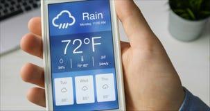 Comprobación del wather usando el smartphone app Tiempo lluvioso y nublado almacen de metraje de vídeo
