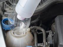 Comprobando el líquido refrigerador del radiador del coche nivele y añada el liqiud Fotos de archivo