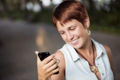 Comprobando el teléfono al aire libre Fotos de archivo libres de regalías
