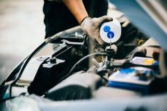 Compruebe el agua en radiador del coche y añada el agua al radiador del coche, sele Foto de archivo libre de regalías