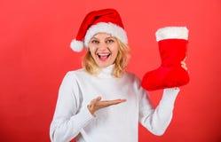 Compruebe el contenido de la media de la Navidad Mujer en fondo del rojo del regalo de la Navidad del control del sombrero de san imagenes de archivo