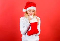 Compruebe el contenido de la media de la Navidad qué ella recibió Mujer en el sombrero de santa que desempaqueta el fondo del roj fotos de archivo libres de regalías