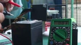 Compruebe la batería de voltio con el multímetro digital almacen de video