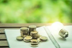 Comptabilité de dépenser le concept d'argent des pièces de monnaie et la note avec l'ampoule, idées créatives pour économiser images stock
