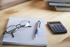 Comptable de lieu de travail Le bloc-notes dans la boîte avec un stylo, la calculatrice, et les verres sur une table en bois à l' Photo stock