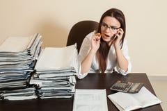 Comptable féminin à l'aide du téléphone portable sur le lieu de travail photo stock