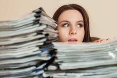 Comptable féminin avec de grandes piles de documents Images stock