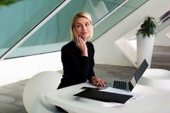 Comptable féminin parlant au téléphone de cellules avant d'établir des rapports mensuels sur l'ordinateur portable photographie stock libre de droits