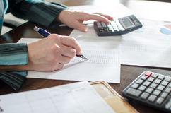 Comptable féminin vérifiant les documents financiers photos stock