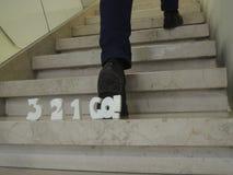 Compte à rebours 3-2-1-go ! derrière l'homme sautant vers le haut des escaliers Images libres de droits