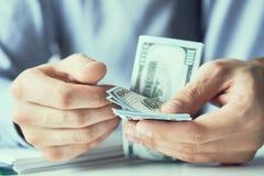Compte d'homme d'affaires le nouveau monnaie fiduciaire de dollars US Forme d'un paiement illicite ou d'un salaire photographie stock libre de droits