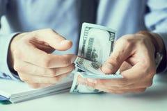 Compte d'homme d'affaires le nouveau monnaie fiduciaire de dollars US Forme d'un paiement illicite ou d'un salaire photo stock