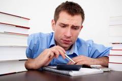 Compte effrayé d'étudiant mâle sur la calculatrice Photos stock