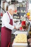 Compteur de Wrapping Cheese At de vendeur dans la boutique Photographie stock libre de droits