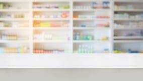 Compteur en bois avec des étagères de tache floue de drogue dans la pharmacie image libre de droits