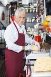 Compteur heureux de Wrapping Cheese At de vendeur dans la boutique Photographie stock libre de droits