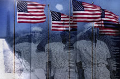 Compuesto de Digitaces: Banderas americanas y reflexión de los marineros que saludan el monumento de guerra de Vietnam de la pare Fotografía de archivo