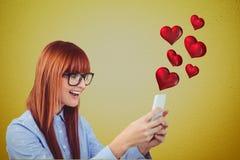 Compuesto de Digitaces de la mujer sonriente que manda un SMS en el teléfono con los corazones rojos Fotografía de archivo