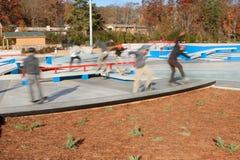 Compuesto de la falta de definición de movimiento de los skateres que gozan del nuevo parque del monopatín imagen de archivo