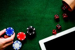 Compulsive gambling. Hand with poker chip and the dice nearby ke. Compulsive gambling. Poker chips and the dice nearby keyboard on green table top view Royalty Free Stock Image