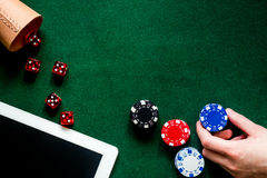 Compulsive gambling. Hand with poker chip and the dice nearby keyboard on green table top view copyspace Royalty Free Stock Photography