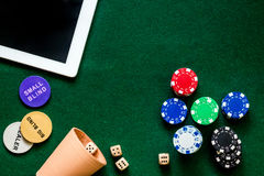 Compulsive gambling. Poker chips and the dice nearby tablet on green table top view copyspace Royalty Free Stock Images
