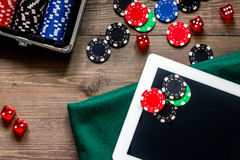 Compulsive gambling. Poker chips and the dice nearby tablet on wooden table top view Stock Image