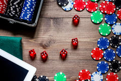 Compulsive gambling. Poker chips and the dice nearby tablet on wooden table top view copyspace Royalty Free Stock Photos