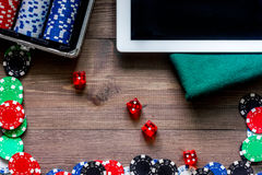 Compulsive gambling. Poker chips and the dice nearby tablet on wooden table top view copyspace Royalty Free Stock Images