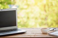 Computador com caderno, vidros e copo do chá ou do café no fundo de madeira da tabela e da natureza imagem de stock