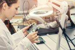 Computador de placa de exame do técnico profissional fêmea bonito do perito de computador em um laboratório em uma fábrica imagem de stock royalty free