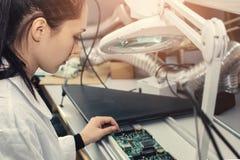 Computador de placa de exame do técnico profissional fêmea bonito do perito de computador em um laboratório em uma fábrica foto de stock royalty free