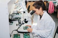 Computador de placa de exame do técnico profissional fêmea bonito do perito de computador em um laboratório em uma fábrica foto de stock