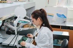 Computador de placa de exame do técnico profissional fêmea bonito do perito de computador em um laboratório em uma fábrica fotos de stock