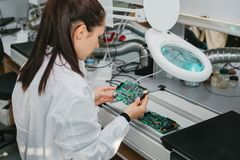 Computador de placa de exame do técnico profissional fêmea bonito do perito de computador em um laboratório em uma fábrica fotografia de stock