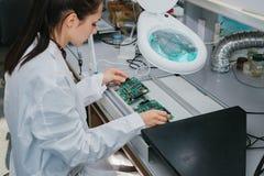 Computador de placa de exame do técnico profissional fêmea bonito do perito de computador em um laboratório em uma fábrica imagens de stock royalty free