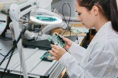 Computador de placa de exame do técnico profissional fêmea bonito do perito de computador em um laboratório em uma fábrica fotos de stock royalty free