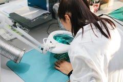 Computador de placa de exame do técnico profissional fêmea bonito do perito de computador em um laboratório em uma fábrica imagem de stock