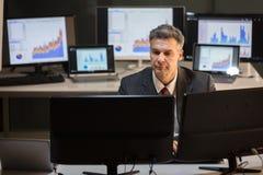 Computador de Working On Multiple do homem de negócios imagem de stock royalty free