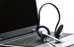 Computador e auriculares Fotos de Stock