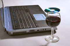 Computador portátil com um vidro do vinho e do CD. fotografia de stock royalty free