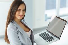 Computador portátil da terra arrendada da mulher de negócio Fotografia de Stock